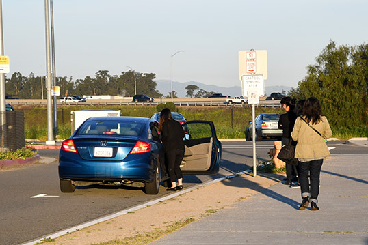 Image of one person getting into car just off of the curb and three people on the curb looking at the car.