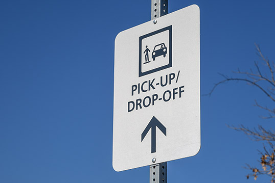 Image of a sign reading pick-up/drop off and an icon of a person on a curb next to a car.