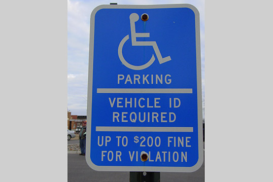 Image of a bright blue sign with an icon of a person in a wheelchair and the words Parking, Vehicle ID Required, Up to $200 fine for violation