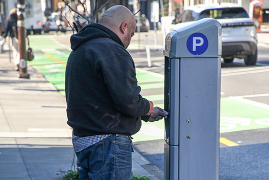 Image of a person paying for parking at a curb-side podium with a large P icon on the side