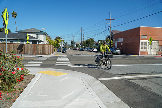 Image of person outside turning a corner on bicycle on a road next to the sidewalk