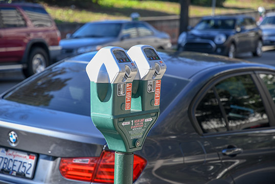 Image of two parking meters with cars parked at them