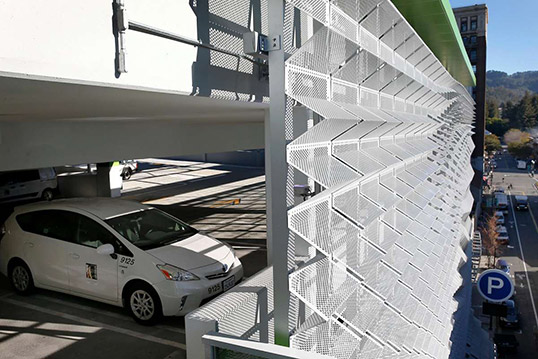 Image of multi-story parking garage with shaded wall to diffuse sunlight on parked cars.