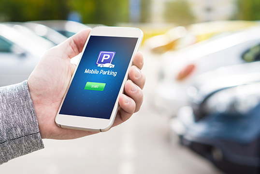 Image of a phone showing landing page for a mobile parking app, in someone's hand with blurry cars in the background