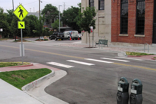 Image of crosswalk on empty road including two curb bulbs and yield sign.