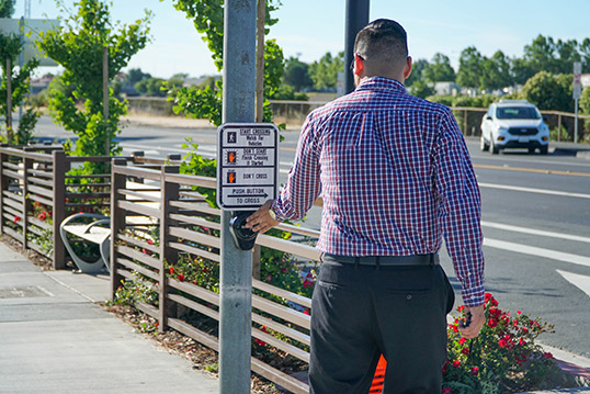 Image of a person pressing the walk button to cross street next to clearly marked signal crossing sign.