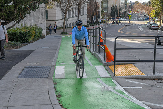 Image of person riding a bike on a bike lane with metal bars protecting them from street traffic.