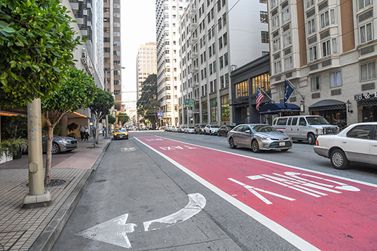 Image of dedicated bus lane shown in red paint, as an example of how changes to the street design can enhance bus reliability.