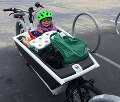 Image of a child and groceries in a cargo bike at a bike rack.