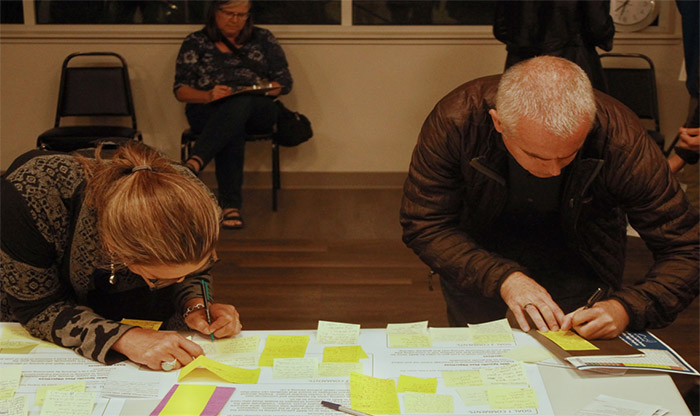 Image of two people writing on sticky notes on a table covered in papers and written-on sticky notes.