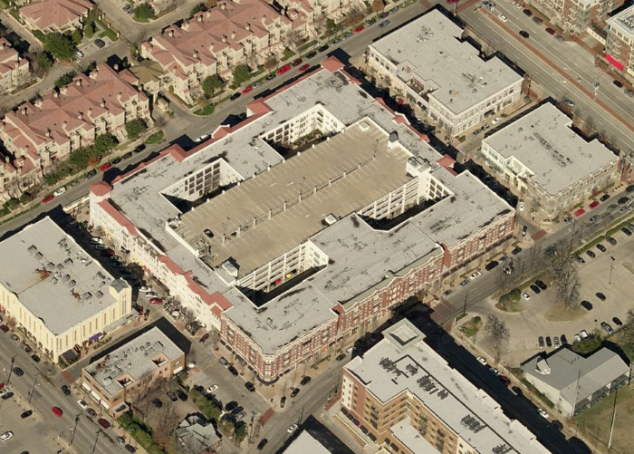 Ariel image of a parking garage with a building wrapped around it and four courtyards