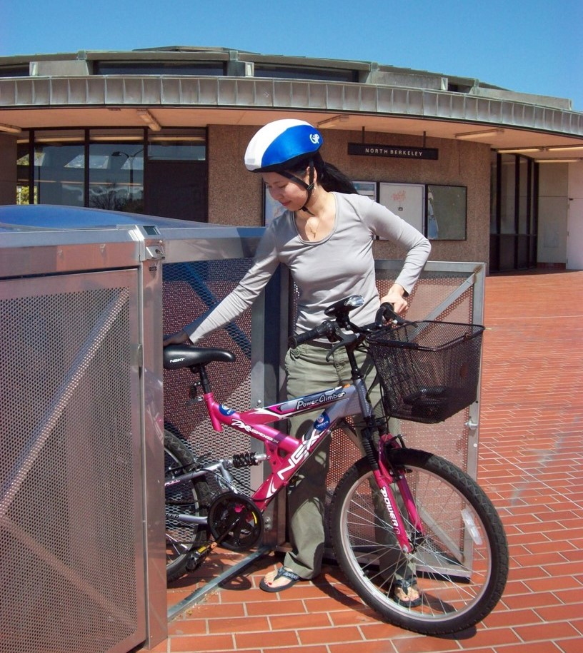 Photo of a person parking a bike in a bike locker at the North Berkeley BART station.