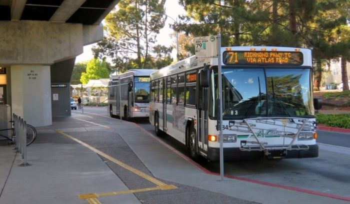 Image of an AC Transit bus in front of the entrance to a BART station.