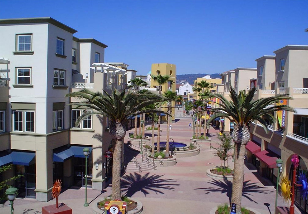 Aeriel image of Fruitvale BART station area after the transit-oriented development was built, with stores in buildings, concrete seating surrounding palm trees, a water feature and sunshine-themed art sculptures.