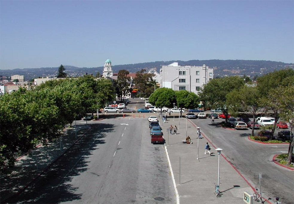 Aeriel image of Fruitvale BART station area before the transit-oriented development was built. It has wide, mostly empty streets with some cars on it lined by trees spread out and a few people walking around.