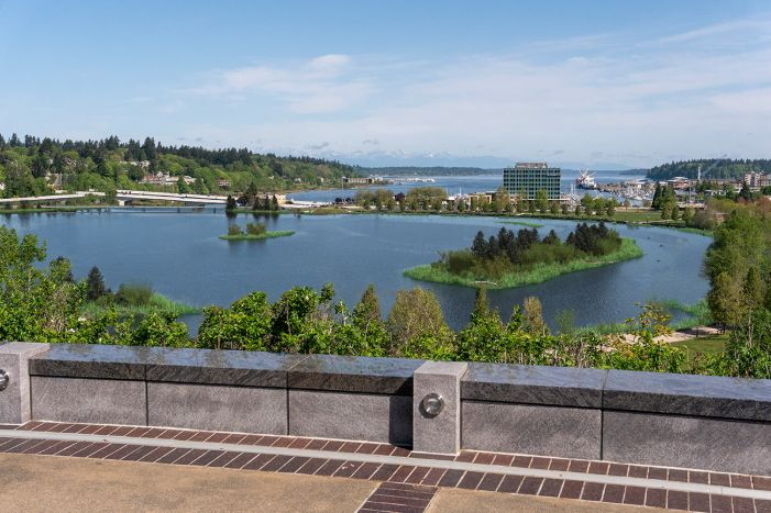 A visual simulation of the Estuary Alternative, looking north toward the North Basin and Budd Inlet. The visual simulation was generated to represent the potential viewshed from a North Overlook on the Washington State Capitol Campus. The North Basin is full of water with habitat areas showing on the eastern shoreline of the North Basin. Birds and new 5th Avenue Pedestrian and vehicle bridges can be seen in the distance.