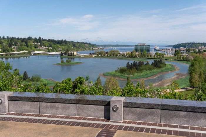 A visual simulation of the Estuary Alternative, looking north toward the North Basin and Budd Inlet. The visual simulation was generated to represent the potential viewshed from a North Overlook on the Washington State Capitol Campus. The North Basin is partially full of water with some tideflats and habitat areas showing on the eastern shoreline of the North Basin. Birds and new 5th Avenue Pedestrian and vehicle bridges can be seen in the distance.