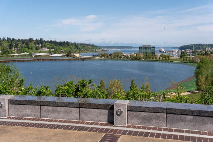 A visual simulation of the Hybrid Alternative, looking north toward the North Basin and Budd Inlet. The visual simulation was generated to represent the potential viewshed from a North Overlook on the Washington State Capitol Campus. The reflecting pool is full of water and a steel sheetpile barrier wall can be seen at approximately center of the North Basin. The estuary can barely be seen in the distance, along with new 5th Avenue Pedestrian and vehicle bridges.