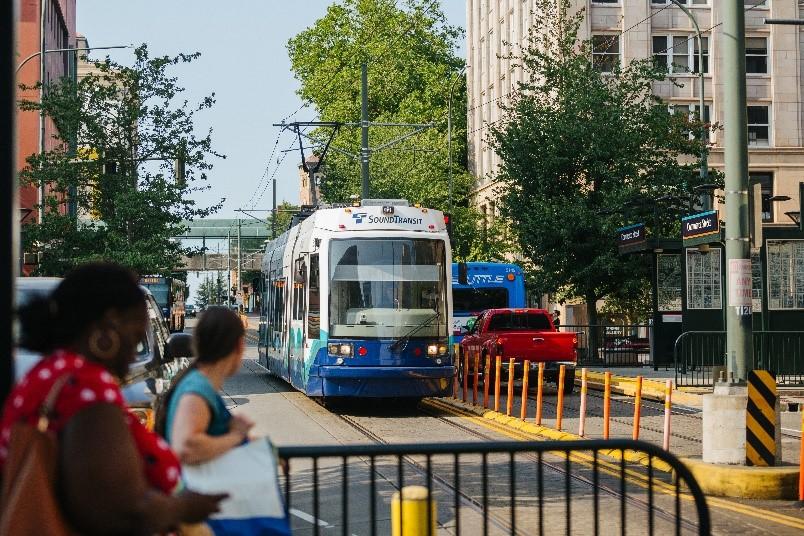 Un tren en un entorno urbano con un grupo de personas que están esperando para abordarlo