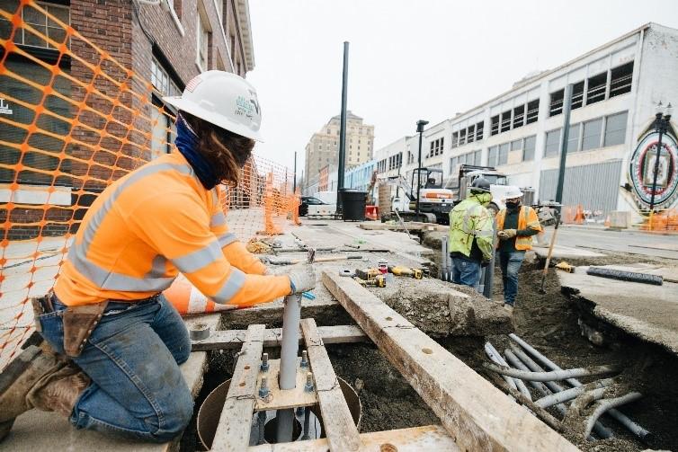 Un trabajador con equipo de seguridad trabaja en una tubería subterránea