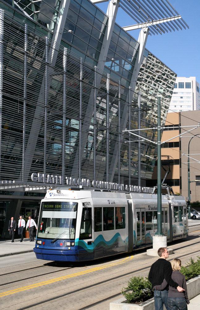 Un tren en un entorno urbano con una pareja caminando en primer plano
